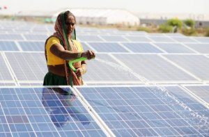 A worker sprays water at India's first 1 megawatt canal-top solar power plant in Chandrasan village.
